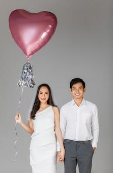 젊은 매력적인 아시아 커플, 흰 셔츠를 입은 남자, 손을 잡고 함께 서 있는 웨딩 베일과 함께 흰 드레스를 입은 여자. 풍선을 들고 여자입니다. 사전 결혼식 사진에 대한 개념입니다.