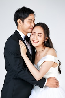 Young attractive asian couple, soon to be bride and groom, woman wearing white wedding gown. man wearing black tuxedo, hugging each other. concept for pre wedding photography.