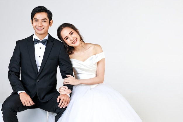 Young attractive asian couple, soon to be bride and groom, woman wearing white wedding gown. man wearing black tuxedo, sitting down together. concept for pre wedding photography.