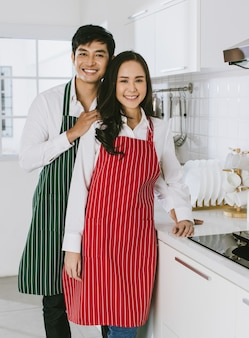 カメラに微笑んで緑と赤のエプロンを身に着けている若い魅力的なアジアのカップル。健康のためのコンセプト