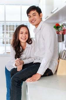 カメラに微笑んでキッチンで白いシャツとジーンズを着ている若い魅力的なアジアのカップル。健康で幸せな愛と料理のコンセプト。