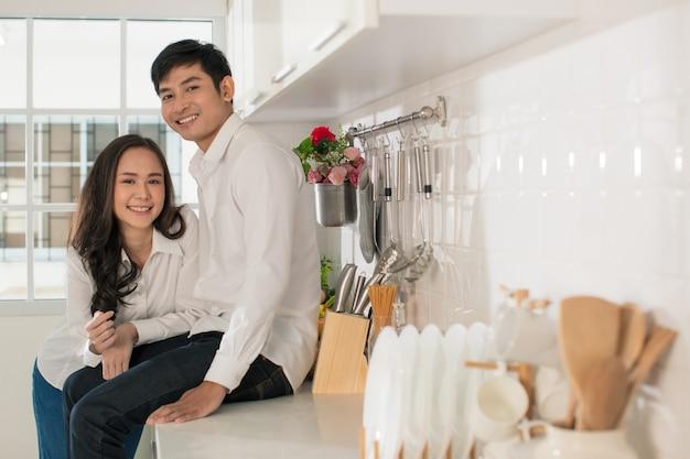 カメラに微笑んでキッチンで白いシャツとジーンズを着ている若い魅力的なアジアのカップル。