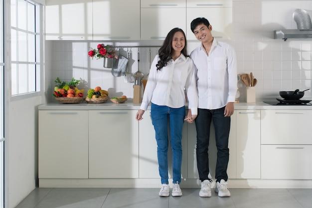 白いキッチンで白いシャツとジーンズを着ている若い魅力的なアジアのカップル。