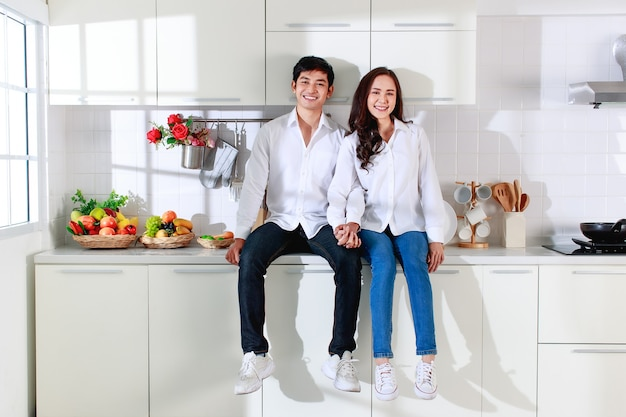 白いキッチンに座っている白いシャツとジーンズを着ている若い魅力的なアジアのカップル。