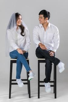 흰색 셔츠와 청바지를 입은 젊은 아시아 부부는 함께 의자에 앉아 흰색 배경에 웃고 있는 웨딩 베일을 쓰고 있습니다. 사전 결혼식 사진에 대한 개념입니다.