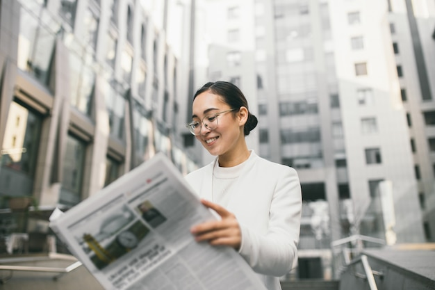 Young attractive asian female banker or accountant in glasses is reading newspaper outside a modern office center or a bank