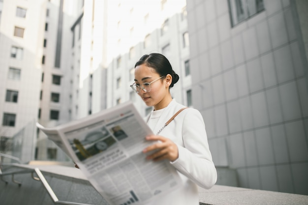 Young attractive asian female banker or accountant in glasses is reading newspaper outside a modern office center