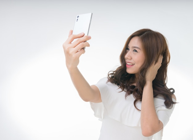 Young attractive asian female taking selfie, on white