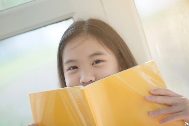 Young attractive asian girl who reading a book at home