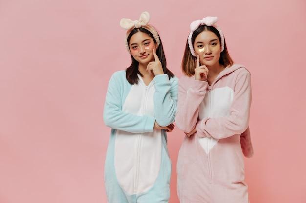 Молодые привлекательные азиатские девушки в косметических повязках на глаза смотрят задумчиво спереди, позируют в пижаме на розовой стене
