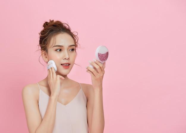 분홍색 배경 위에 파우더 퍼프로 얼굴에 블러셔를 바르는 젊은 매력적인 아시아 여성.