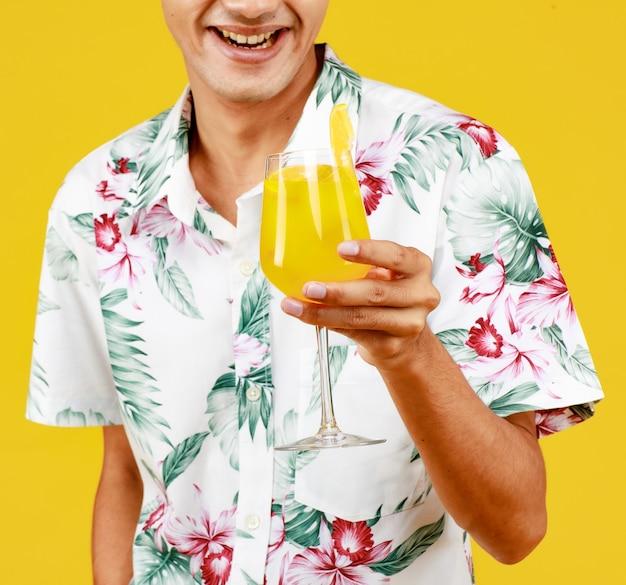 노란색 배경에 오렌지 주스 한 잔을 들고 흰색 하와이안 셔츠에 젊은 매력적인 아시아 남자. 해변 휴가 휴가에 대한 개념입니다.