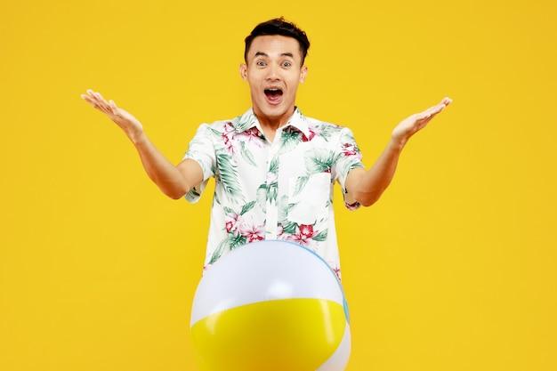 노란색 배경에 비치 볼을 들고 흰색 하와이안 셔츠에 젊은 매력적인 아시아 남자. 해변 휴가 휴가에 대한 개념입니다.