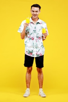 노란색 배경에 오렌지 주스 두 잔을 들고 흰색 하와이안 셔츠를 입은 젊은 매력적인 아시아 남자. 해변 휴가 휴가에 대한 개념입니다.