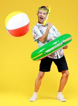 흰색 하와이안 셔츠를 입은 젊고 매력적인 아시아 남자는 노란색 스노클링 마스크와 노란색 배경에 공을 들고 허리 둘레에 녹색 수영 링을 착용합니다. 해변 휴가 휴가에 대한 개념입니다.