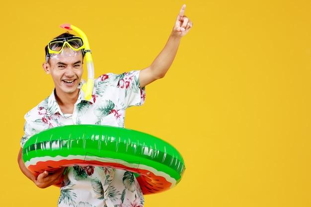 흰색 하와이안 셔츠를 입은 젊고 매력적인 아시아 남자는 노란색 스노클링 마스크와 허리에 녹색 수영 반지를 착용하고 노란색 배경에 대해 손가락으로 공기를 가리킵니다. 해변 휴가 휴가에 대한 개념입니다.