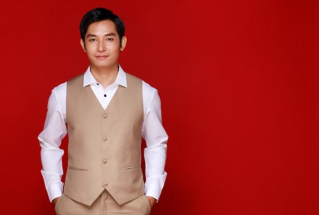 すぐに若い魅力的なアジア人男性は、赤い背景に白いシャツとベージュのベストを着て新郎になります。結婚式前の写真撮影のコンセプト。