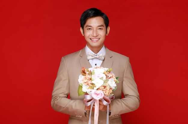 若い魅力的なアジア人男性はすぐに白いシャツとベージュのベストと赤い背景に花の花束を保持しているスーツを着て新郎になります。結婚式前の写真撮影のコンセプト。