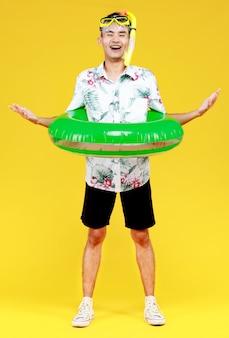모자와 흰색 하와이안 셔츠를 입은 젊은 매력적인 아시아 남자는 노란색 스노클링 마스크와 노란색 배경에 대해 허리에 녹색 수영 링을 두르고 있습니다. 해변 휴가 휴가에 대한 개념입니다.