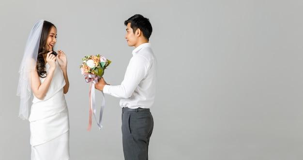 흰 셔츠를 입은 젊은 매력적인 아시아 남성이 흰 드레스와 깜짝 얼굴을 한 웨딩 베일을 입은 여성에게 꽃다발을 건네줍니다. 제안 및 사전 결혼 사진에 대한 개념입니다.