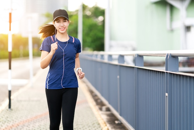 Young attractive asian runner woman running in city street