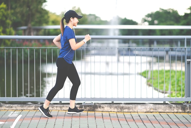 Young attractive asian runner woman running at sidewalk way