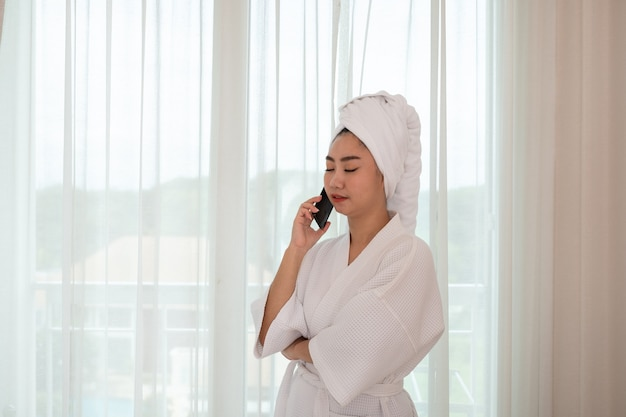 Young attractive asian woman in a bathrobe standing and talking on the phone at the living room