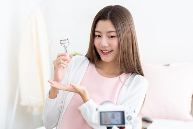Молодой привлекательный азиатский влияния красоты женщины держа curler ресницы делая течь в реальном маштабе времени перед камерой