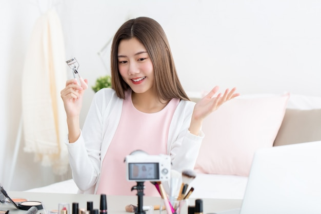 Vlogger молодой привлекательной азиатской красоты женщины держа curler ресницы делая течь в реальном маштабе времени перед камерой