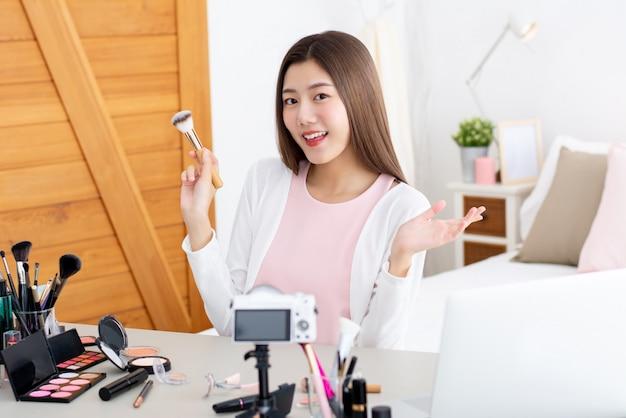 Молодое привлекательное азиатское удерживание vlogger красоты женщины составляет щетку делая течь в реальном маштабе времени перед камерой