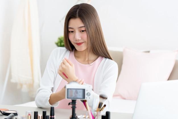 Молодая привлекательная азиатская губная помада испытания красоты женщины на задней части ее руки перед камерой