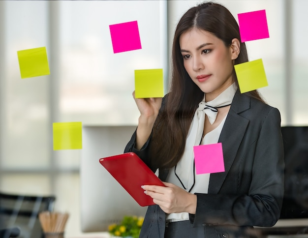 Young attractive asian woman in black business writing on post it on glass panel one hand holding tablet in modern looking office with blurry windows background. concept for modern office lifestyle.
