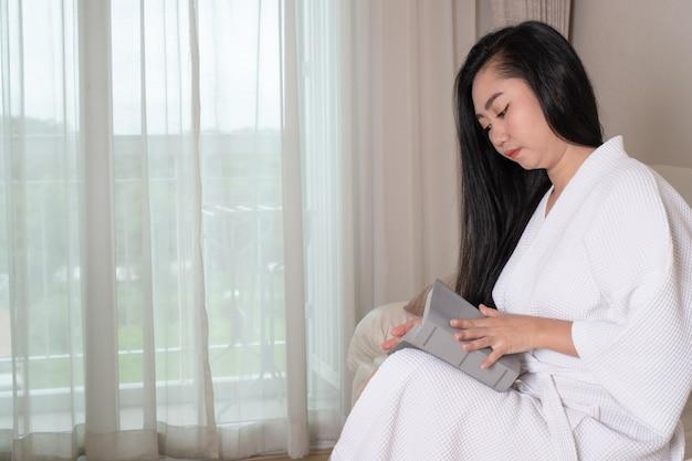 Молодая привлекательная азиатская женщина в халате сидит на диване и читает книгу в гостиничном номере