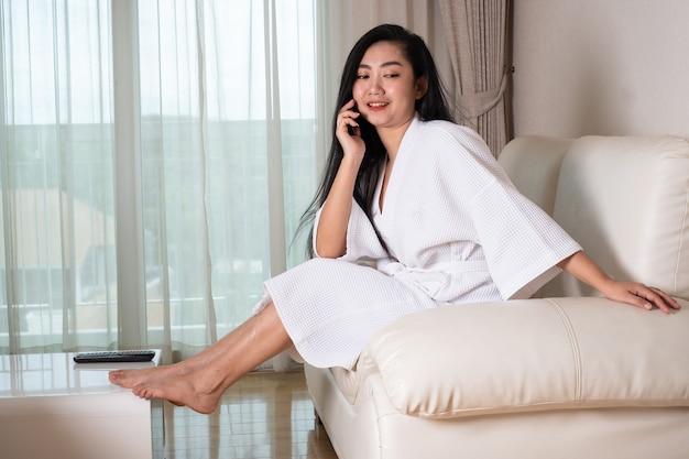 Молодая привлекательная азиатская женщина в халате сидит на диване, разговаривает по телефону в комнате