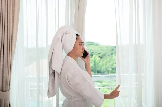 Молодая привлекательная азиатская женщина в халате стоит и разговаривает по телефону в гостиной