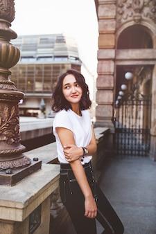 Молодая привлекательная азиатская женщина в белой футболке и черных джинсах в историческом здании