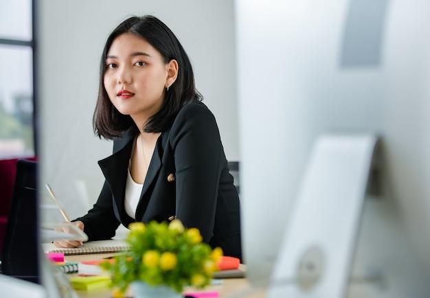 現代のオフィスに座って、テーブルの上のラップトップで働いて笑っている黒いビジネススーツの若い魅力的なアジアの女性。現代のオフィスライフスタイルのコンセプト。