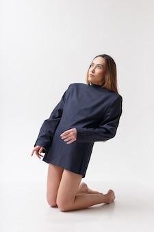 スタジオで彼女の膝の上に立っている青いスーツの若い魅力的なアジアの女性