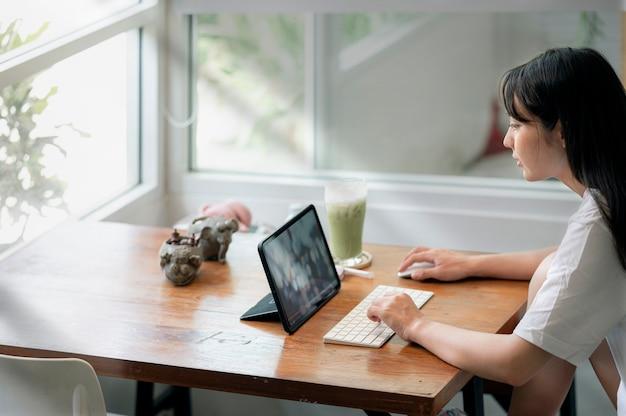 집에 있는 거실에 앉아 컴퓨터를 사용하여 캐주얼한 옷을 입은 젊은 매력적인 아시아 여성, 온라인 학습 개념.