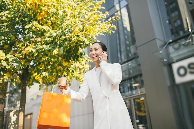 Молодая привлекательная азиатская женщина выходит из модного магазина, разговаривает по телефону и держит кофе и сумки