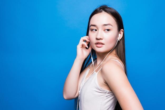 Musica d'ascolto della giovane donna asiatica attraente sulla parete blu