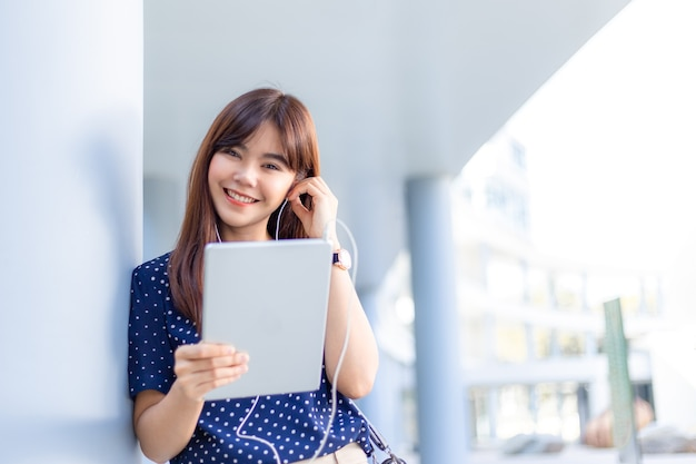 Young attractive asian woman listening to music from her computer tablet outside of her office