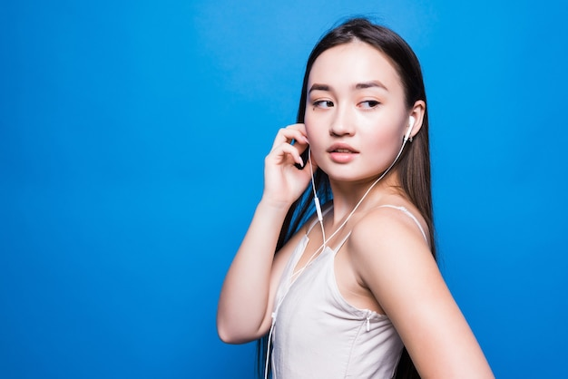 파란 벽에 젊은 매력적인 아시아 여자 듣기 음악