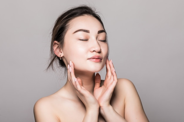 Young attractive asian woman skin care on gray wall