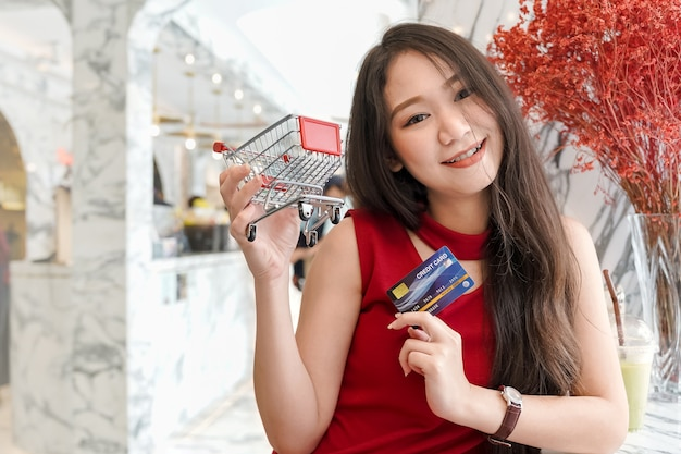 Young attractive asian woman smiling holding credit card and shopping cart while relax in cafe
