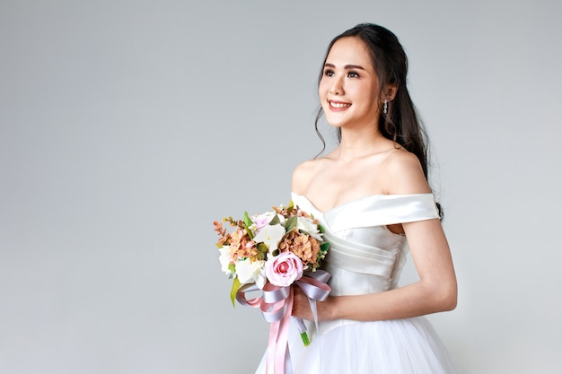 Young attractive asian woman, soon to be bride, wearing white wedding gown looking happy holding bouquet of flower. concept for pre wedding photography.