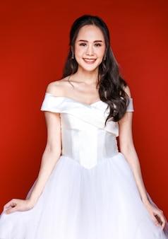 赤い背景に花の花束を保持している白いウェディングドレスを着てすぐに花嫁になる若い魅力的なアジアの女性。結婚式前の写真撮影のコンセプト。