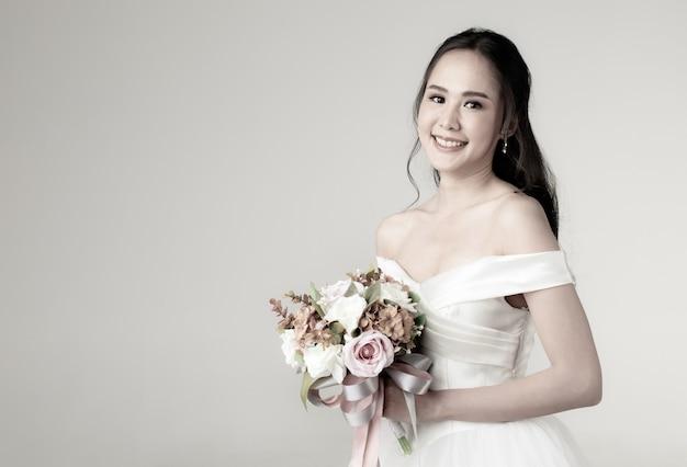 花の花束を持って幸せそうに見える白いウェディングドレスを着て、すぐに花嫁になる若い魅力的なアジアの女性。結婚式前の写真撮影のコンセプト。