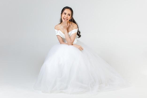 すぐに花嫁になる若い魅力的なアジアの女性は、幸せそうに見えて座って白いウェディングドレスを着ています。結婚式前の写真撮影のコンセプト。