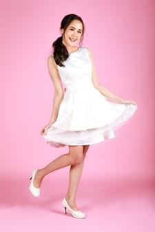 ピンクの背景に白いウェディングドレスを着ている若い魅力的なアジアの女性。結婚式前の写真撮影のコンセプト。